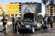 "Picture released by the official Syrian Arab News Agency (SANA) July 13, shows police inspecting the site of a car bomb explosion on Mazzeh highway in the capital Damascus. Peace envoy Kofi Annan said Syria had ""flouted"" Security Council resolutions with mass killings in Treimsa village, as UN chief Ban Ki-moon demanded that the Council act to stop the bloodshed"