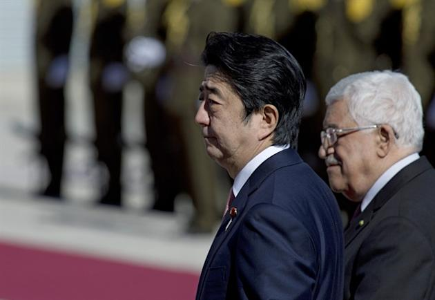Palestinian President Mahmoud Abbas, right, escorts Japanese Prime Minister Shinzo Abe upon his arrival at the Palestinian Authority headquarters, in the West Bank city of Ramallah, Tuesday, Jan. 20, 2015. An online video released Tuesday purported to show the Islamic State group threatening to kill two Japanese hostages unless they receive a $200 million ransom in the next 72 hours. (AP Photo/Nasser Nasser)