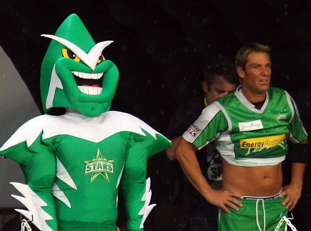 MELBOURNE, AUSTRALIA - JANUARY 07:  Shane Warne of the Stars is miked up for television as he stands next to the Stars mascot during the T20 Big Bash League match between the Melbourne Stars and the M
