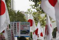 "A member of the nationalist movement ""Ganbare Nippon"" holding a placard of disputed islands known as Senkaku in Japan and Diaoyu in China, walks among Japanese national flags during a rally in Tokyo September 11, 2013, on the day of one year anniversary of Japanese government signed contract to buy islands disputed with China from a private owner. China said it would not tolerate provocation after Japan's top government spokesman said on Tuesday Japan might station government workers on disputed islands in the East China Sea to defend its sovereignty. Relations between the world's second- and third-biggest economies have been strained over the uninhabited isles which Japan controls but both countries claim. Placard reads, ""No TPP (Tran-Pacific Partnership), No sales Tax hike, Protect our national interest, Senkaku islands are Japanese territories, Don't permit Chinese territorial waters violation."" REUTERS/Toru Hanai (JAPAN - Tags: POLITICS CIVIL UNREST)"