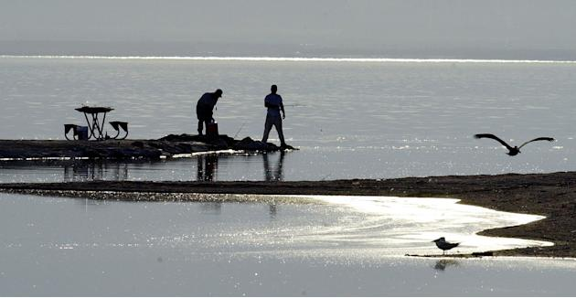 A fishermen works off a jetty in the Salton Sea Recreation Area on the Salton Sea's eastern shore in California, 2002. (AP Photo/Reed Saxon, File)