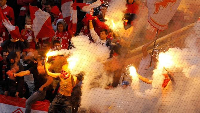 Spartak fans burn flares while celebrating their team's goal against CSKA during a Russian Premier League Championship soccer match between CSKA Moscow and Spartak Moscow at the Lokomotiv stadium in Moscow, Russia, Sunday, Sept. 22, 2013. Spartak won 3-0