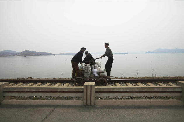 In this April 21, 2011 photo, men operate a manual rail car on tracks running along the West Sea barrage near Nampho, North Korea. (AP Photo/David Guttenfelder)