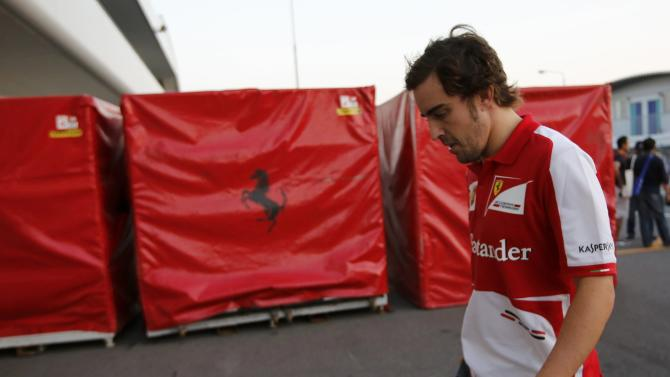 Ferrari Formula One driver Alonso of Spain walks on the paddock after the Japanese F1 Grand Prix at the Suzuka circuit