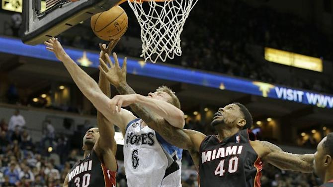 Minnesota Timberwolves forward Robbie Hummel (6)  battles Miami Heat forward Udonis Haslem (40) and guard Norris Cole (30) for a rebound during the fourth quarter of an NBA basketball game in Minneapolis, Saturday, Dec. 7, 2013. The Heat won 103-82
