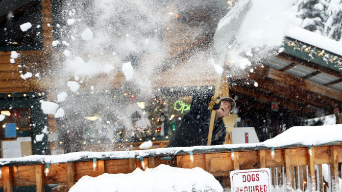 Don McLachlan shovels out from a winter snow storm at Shelter Cover Resort and Marina on Willamette Pass after a snow storm descended on the area Monday, Dec. 17, 2012. (AP Photo/The Register-Guard, Chris Pietsch)