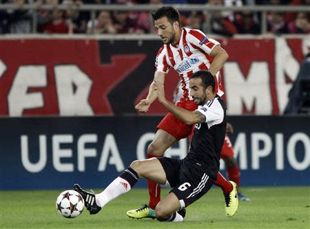 Olympiakos Piraeus' Samaris fights for the ball against Benfica's Amorim during their Champions League soccer match in Piraeus near Athens