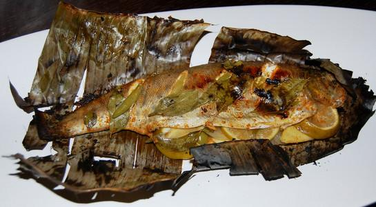 Grilled trout in banana leaf