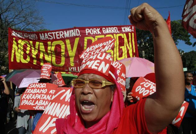 A protester clenches her fist while shouting anti-government slogans during a rally on International Women's Day in Manila