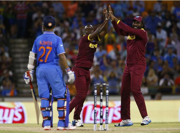 West Indies bowler Kemar Roach celebrates with team mate Chris Gayle after India's batsman Ajinkya Rahane was caught behind by wicketkeeper Denesh Ramdin during their Cricket World Cup match in Pe