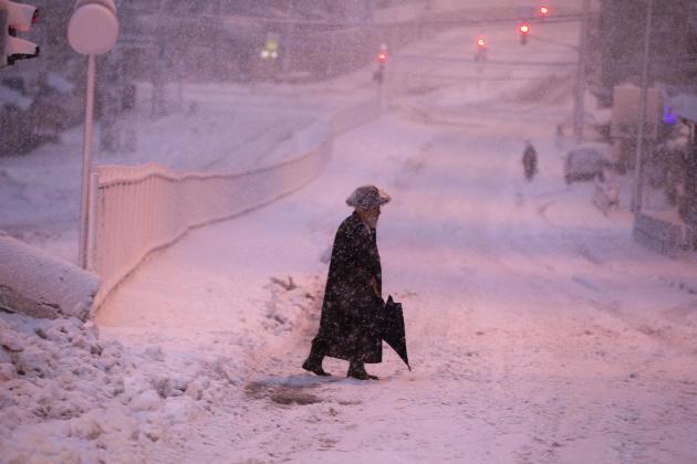 An ultra-Orthodox Jewish man walks on a snow-covered street early morning near Jerusalem's Mea Shearim neighbourhood