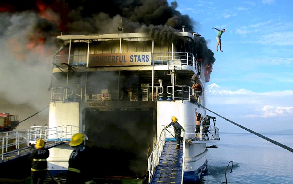 A crew member of MV Wonderful Stars ship jumps off from the burning ship after a fire broke out at the port in Ormoc city, central Philippines