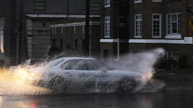 A car drives through standing water, Monday, Nov. 19, 2012, at an intersection in Tacoma, Wash. Wet and windy weather with mountain snow will continue this week in Washington, forecasters said. (AP Photo/Ted S. Warren)