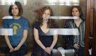 """The three members of the Russian punk band """"Pussy Riot"""" -- Nadezhda Tolokonnikova (left), Maria Alyokhina (centre) and Yekaterina Samutsevich -- sit inside a glass enclosure during a court hearing in Moscow"""
