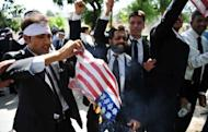 Pakistani lawyers burn a US flag as they attempt to reach the US embassy in the diplomatic enclave during a protest against an anti-Islam movie in Islamabad. As protests again erupted across the Muslim world on Wednesday over an anti-Islam film, a French magazine poured fuel on the fire by publishing obscene cartoons depicting the Prophet Mohammed