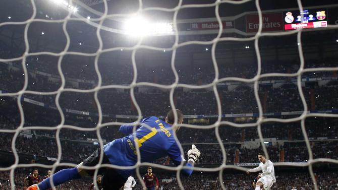 Real Madrid's Cristiano Ronaldo scores a penalty goal against Barcelona's goalkeeper Victor Valdes during La Liga's second 'Clasico' soccer match of the season at Santiago Bernabeu stadium in Madrid