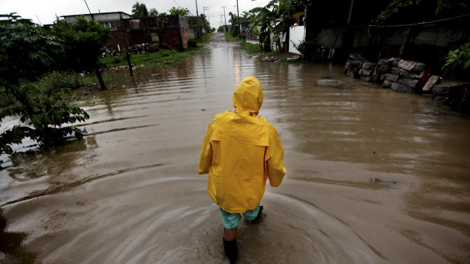 Ismael Vela Hernandez, 60, walks through flooded streets as he tries to make his way home after heavy rains caused by Tropical Storm Barry in the city of Veracruz, Mexico, Thursday June 20, 2013. Barry has weakened to a tropical depression but is still producing torrential rains. (AP Photo/Felix Marquez)