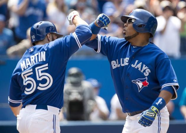 Toronto Blue Jays DH Edwin Encarnacion, right, celebrates his two-run home run with teammate Russell Martin, left, against the Seattle Mariners during fifth inning AL baseball action in Toronto on Sun