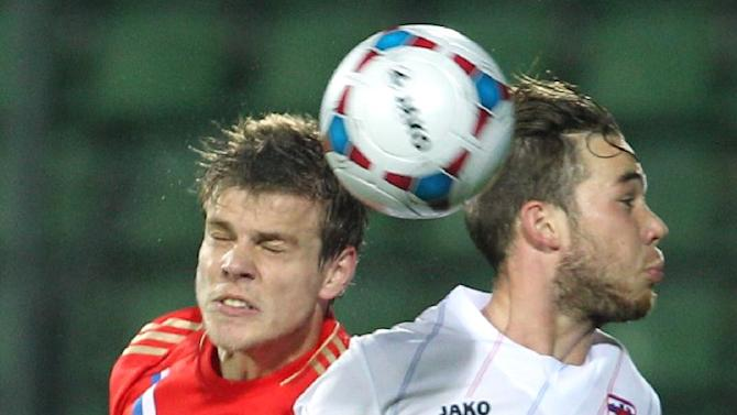 Luxembourg's Tom Laterza, right, is challenged by Russia's Alexander Kokorin, as they head for the ball, during their World Cup 2014 Group F qualifying soccer match in Luxembourg city, at the Josy Barthel stadium, Friday, Oct. 11, 2013