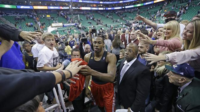 Houston Rockets' Dwight Howard hands his jersey to a fan as he walks off the court following their NBA basketball game against the Utah Jazz, Saturday, Nov. 2, 2013, in Salt Lake City. The Rockets defeated the Jazz 104-93