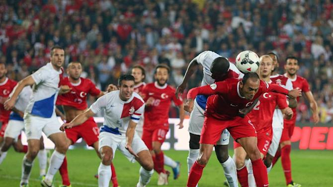 Turkey's Umut Bulu, front-right, and  Bruno Martins Indi of Netherlands, top, fight for the ball during their World Cup Group D qualifying soccer match at Sukru Saracoglu Stadium in Istanbul, Turkey,  Tuesday, Oct. 15, 2013. (AP Photo)
