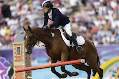 Hwang Woojin, of South Korea, and his horse Shearwater Oscar, knock down a pole in the equestrian show jumping stage of the men's modern pentathlon at