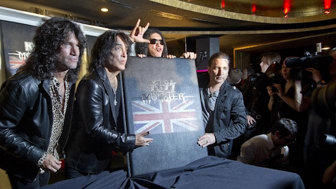 U.S rock band KISS members, from left, Tommy Thayer, Paul Stanley, Gene Simmons and Eric Singer, with their new book 'Monster' which contains photographs of the band's 40 year career live on stage, following a press conference in London, ahead of a concert on July 4 in aid of Help For Heroes. (AP Photo/Joel Ryan)
