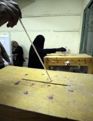 An Egyptian woman wearing the niqab casts her vote as an official pushes votes to allow more space in the ballot box at a polling center in Giza, Egypt Thursday, Dec. 15, 2011. Egyptians have turned out in large numbers for a second round of parliamentary elections, with Islamists looking to boost their already overwhelming lead and liberal voters concerned the outcome will push the country in a more religious direction. (AP Photo/Amr Nabil)