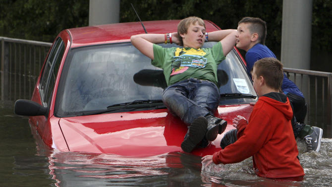 "FILE - In this Thursday, June 28, 2012 file photo, children play on a stranded car in the flood water as torrential downpours cause flash floods in Jarrow, England. Come rain, wind or sunshine, weather has long been Britain's main topic of conversation. Now it has also become a mystery. Meteorologists and climate scientists are meeting Tuesday to discuss why this country has recently experienced icy winters, washed-out summers and the coldest spring in half a century. Scientist Stephen Belcher, who's chairing the workshop, says its goal is to look at whether the weird weather is the result of ""a run of natural variability,"" or the product of human-driven climate change.(AP Photo/Scott Heppell, File)"