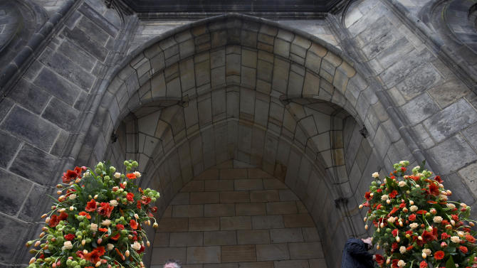 Floral arrangements are made at the entrance of Nieuwe Kerk in Amsterdam, Netherlands, Monday, April 29, 2013. Netherlands' Queen Beatrix will step down on April 30, 2013, leaving the monarchy to her son Crown Prince Willem Alexander. (AP Photo/Peter Dejong)