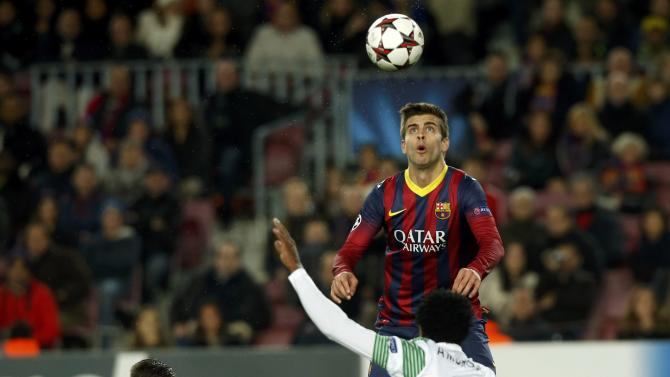 Barcelona's Pique looks at the ball between Celtic's Ambrose and Lustig during their Champions League soccer match in Barcelona