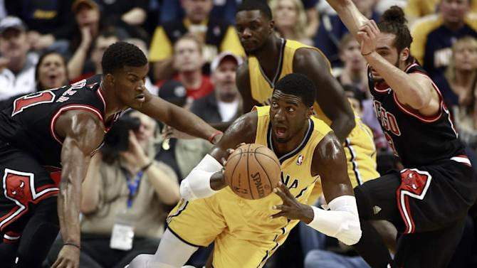 Indiana Pacers center Roy Hibbert passes the basketball while falling as Chicago Bulls guard Jimmy Butler, left, and center Joakim Noah, right, defend during the first half of an NBA basketball game in Indianapolis, Friday, March 21, 2014