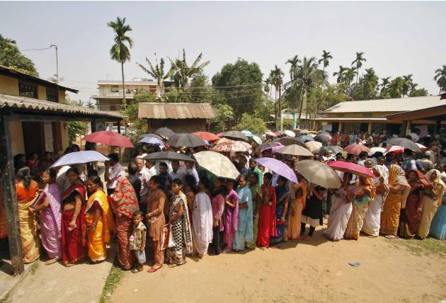 People stand in a queue as they wait to cast their vote outside a polling station at Guwahati