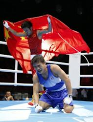 Kaeo Pongprayoon of Thailand (in blue) reacts as Zou Shiming of China (in red) waves the Chinese national flag after being declared winner in the Light Flyweight (49kg) boxing final of the 2012 London Olympic Game. Zou won the gold medal on a 13-10 points decision
