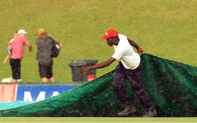A ground worker pulls the covers over the wicket as rain begins to fall just before the end of the second day of the South Africa versus Australia cricket test match at Centurion Park in Pretoria, Sou