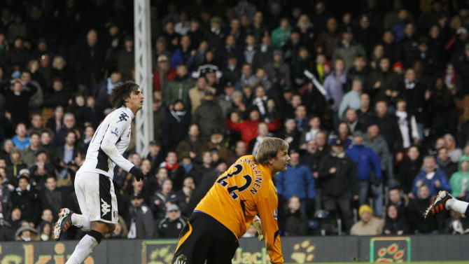 Fulham's Bryan Ruiz, left, reacts as he scores a goal past  Bolton Wanderer's goalkeeper Jussi Jaaskelainen during their English Premier League soccer match at Fulham's Craven Cottage stadium in London, Saturday, Dec.  17, 2011. (AP Photo/Alastair Grant)
