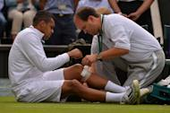 France's Jo-Wilfried Tsonga recieves attention to his leg during a medical time out in his match against Latvia's Ernests Gulbis during their second round men's singles match on day three of the 2013 Wimbledon Championships tennis tournament at the All England Club in Wimbledon, southwest London, on June 26, 2013
