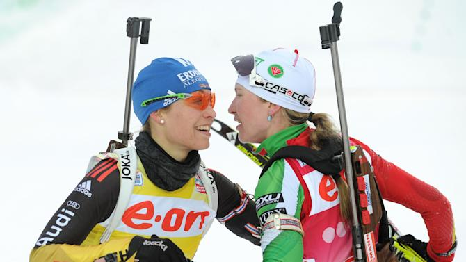 Belarus' Darya Domracheva (R) celebrates with Germany's Magdalena Neuner after winning the women's 12.5 km mass start event of the Biathlon Word Cup in the Siberian city of Khanty-Mansiysk, on March 18, 2012.  Domracheva came home first in 39min 01.4sec despite three mistakes on the shooting range. Germany's Magdalena Neuner, the season's overall World Cup winner, finished sixth at 56sec off the pace with six mistakes.  AFP PHOTO / KIRILL KUDRYAVTSEV (Photo credit should read KIRILL KUDRYAVTSEV/AFP/Getty Images)
