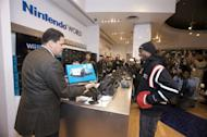 Reggie Fils-Aime, president and COO of Nintendo of America, presents the first Wii U sold in the world to Isaiah Triforce Johnson of Brooklyn, NY, minutes after midnight at the official launch event at Nintendo World in New York on November 18, 2012