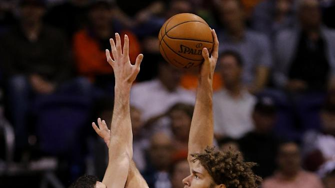 Phoenix Suns' Miles Plumlee, left, defends as Portland Trail Blazers' Robin Lopez shoots during the second half of an NBA basketball game, Wednesday, Nov. 27, 2013, in Phoenix