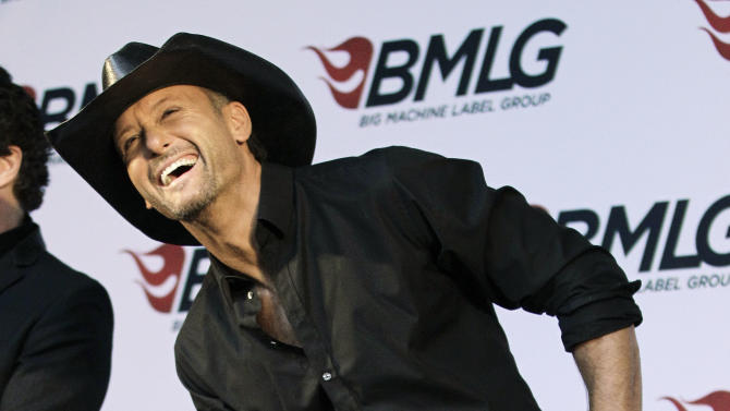 Country music star Tim McGraw laughs at a comment made during a news conference at the Country Music Hall of Fame and Museum on Monday, May 21, 2012, in Nashville, Tenn. It was announced at the news conference that McGraw has signed a multi-album deal with Big Machine Records, officially ending his rocky relationship with his only previous label, Curb Records. (AP Photo/Mark Humphrey)