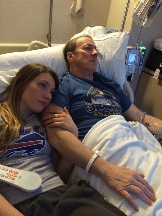This recent photo provided by Jill Kelly shows Jim Kelly, right, at a hospital with his daughter, Erin. Hall of Fame quarterback Jim Kelly is expected to undergo surgery following the return of oral c