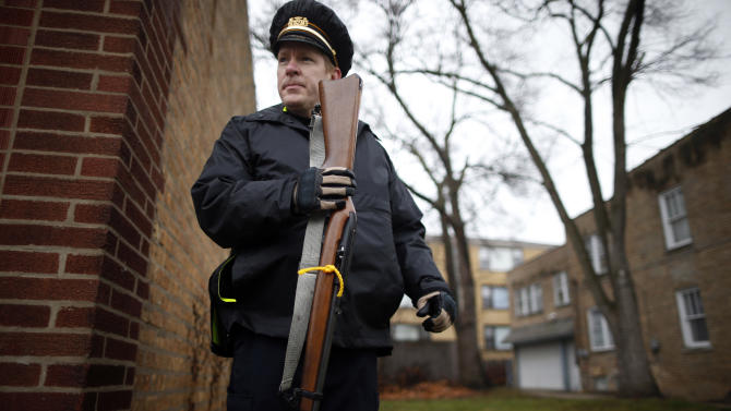 Evanston police officer holds a firearm that was turned in as part of an amnesty-based gun buyback program in Evanston, Illinois
