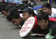 "Protesters shout slogans as they execute ""planking"" by lying prone on the pavement during a rally near the Presidential Palace in Manila, Philippines Friday Sept. 23, 2011 to protest budget cuts in education for state universities and colleges in the country. The students, who walked out of their classes and then marched towards the Presidential Palace, assailed the Government for its alleged bigger slice of this year's national budget to national defense and asserted higher state subsidy on basic social services instead. (AP Photo/Bullit Marquez)"