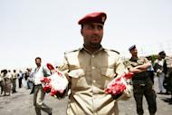 A Yemeni military policeman shows his bloodied gloves as he and colleagues collect evidence at the site of a suicide bomb attack in Sanaa on Monday. A Yemeni soldier packing powerful explosives under his uniform blew himself up in the middle of an army battalion in Sanaa, killing 96 troops and wounding around 300, a military official and medics say