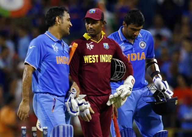 India's batsmen Ravichandran Ashwin and MS Dhoni walk with West Indies' wicket keeper Denesh Ramdin off the field together following India's four wicket victory at the Cricket World Cup in