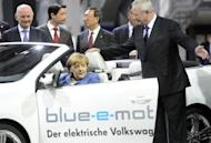 Chancellor Angela Merkel inspects an electric car during a visit to the Volkswagen plant in Wolfsburg, central Germany, in April. Europe's biggest car maker, said Thursday that bottom-line profits in the first half of the year soared by more than a third, leading it to confirm its upbeat forecast for 2012