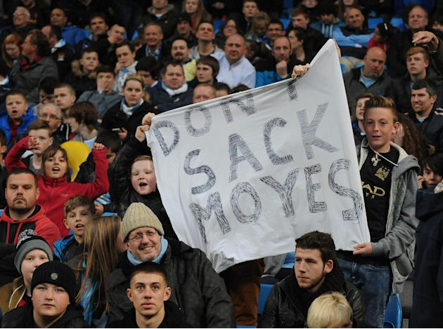 Manchester City supporters display a banner with reference to Manchester United manager David Moyes, during the English Premier League soccer match between Manchester City and West Bromwich at the Eti
