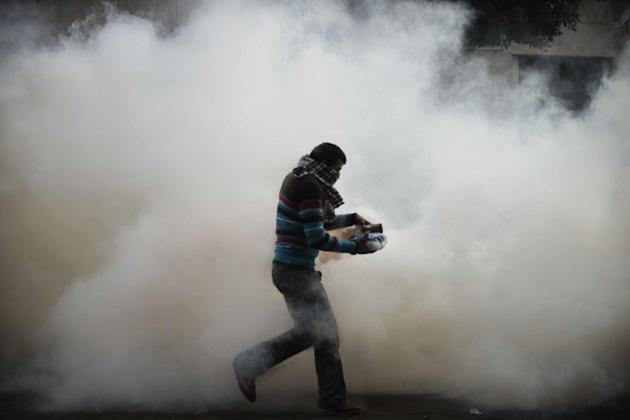 An Egyptian protester attempts to throw back a tear gas canister on November 27