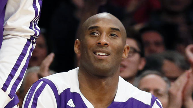 Los Angeles Lakers' Kobe Bryant reacts from the bench after teammate Xavier Henry scored while being fouled against the Toronto Raptors during the first half of an NBA basketball game in Los Angeles, Sunday, Dec. 8, 2013